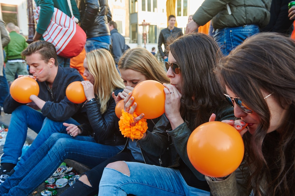 Picture of young people inhaling from balloons